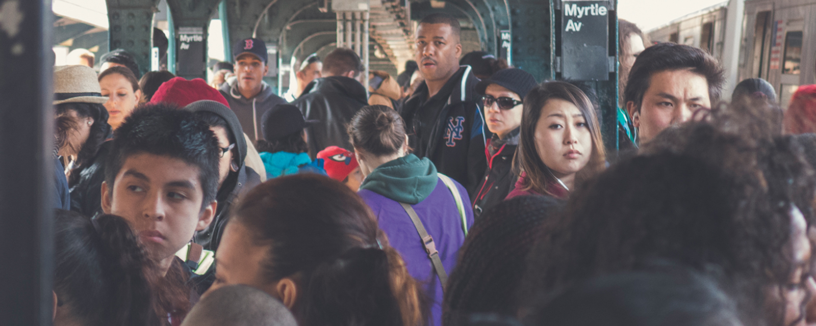 A crowd of people at a subway stop in New York