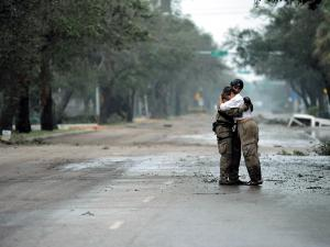 Photo of pararescueman Staff Sgt. Lopaka Mounts receiving a hug from a resident after Hurricane Ike, Sept. 13, 2008.
