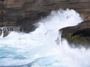 Waves crashing into basaltic rocks from lava flows on Hawai'i Island