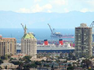 Skyline of highrise buildings and shipping cranes with mountains in the background