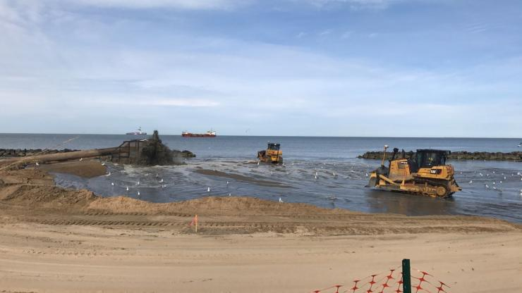 Heavy equipment moving sand on a beach