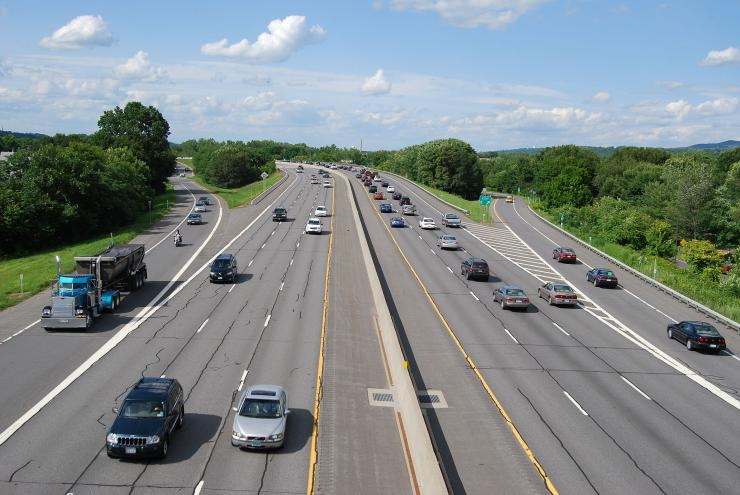 Photo of cars on a six-lane highway with entrance and exit ramps