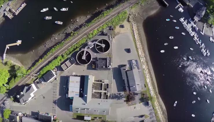 Aerial view of water tanks and buildings surrounded by water with recreational boats.