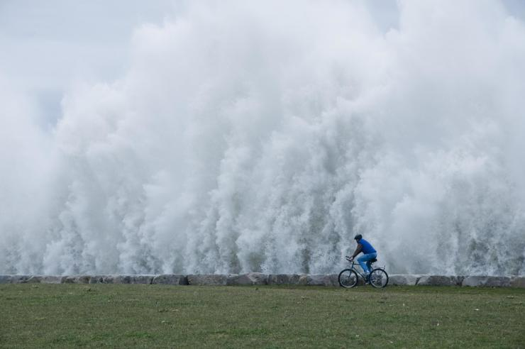 A man riding his bicycle beside an apparent wall of water as winds kick up 20-foot waves along the shores of Lake Michigan.