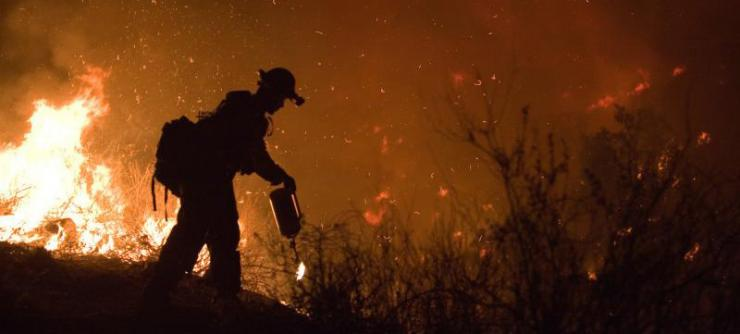 Silhouette of fire crew member against backdrop of fire and smoke
