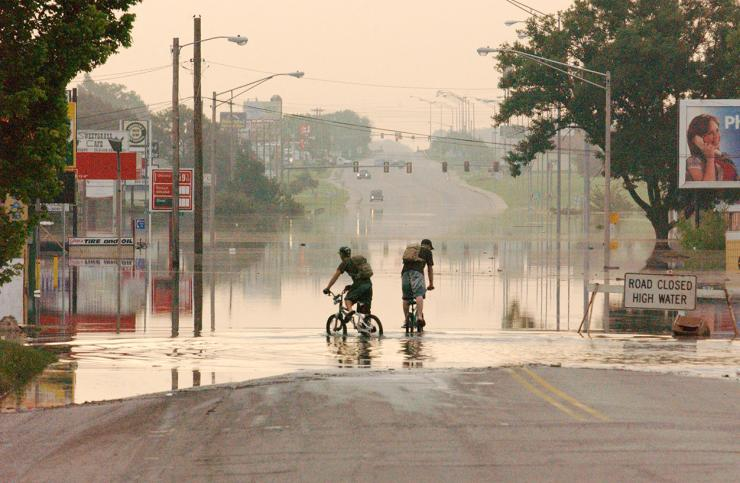 People riding bicycles through a flooded street in Miami, OK