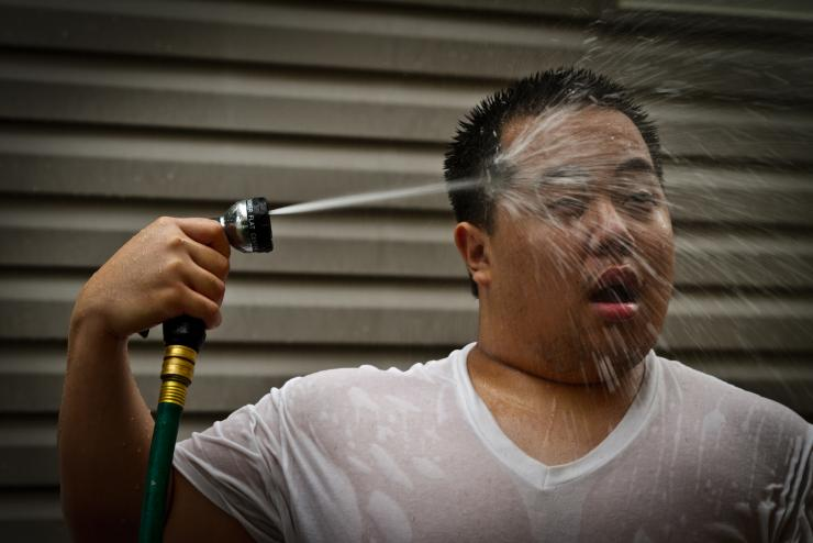 A man spraying himself with a garden hose during a heat wave