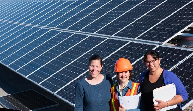 Three women standing in front of an installed solar grid
