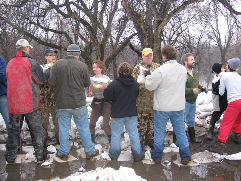 Photo of people passing sandbags
