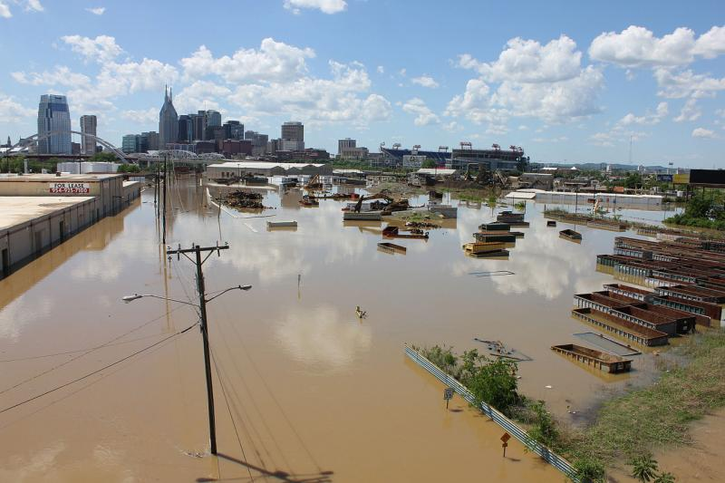 Flooding of industrial area with high-rise buildings in background