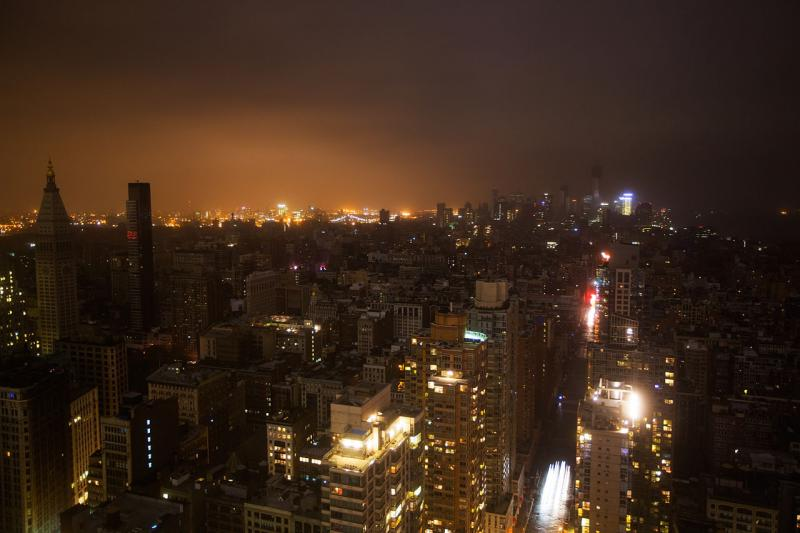 Nightime photo of dense city buildings, many of which are dark