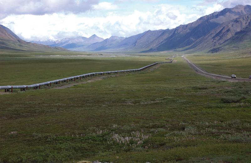 Sub-parallel pipeline and roadway cross a plain with mountains in the distance