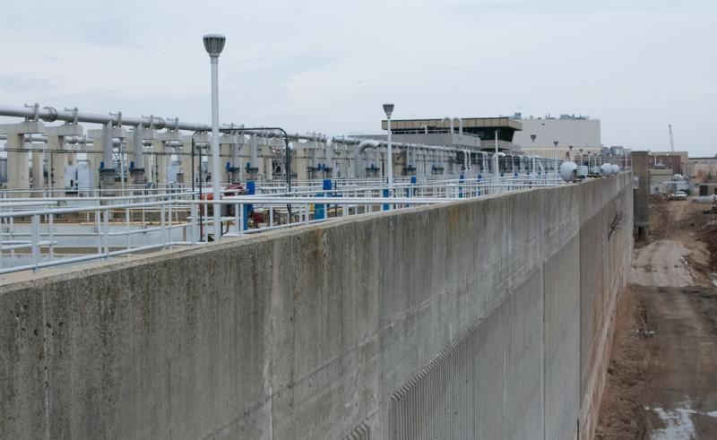 Wastewater treatment equipment adjacent to high concrete wall