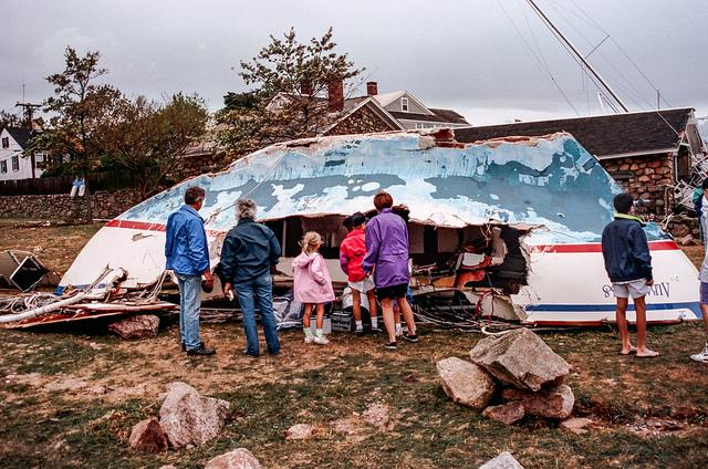 Family standing by damaged sailboat
