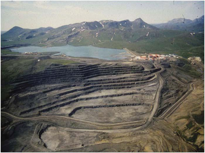 A large section of land has been removed by strip mining near a lake with mountains in the background