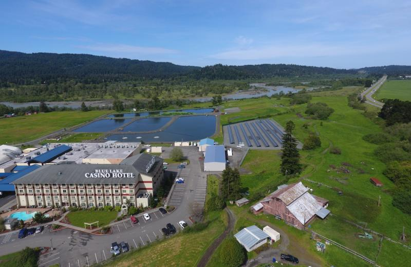 Casino, solar array, river, and mountains under a blue sky