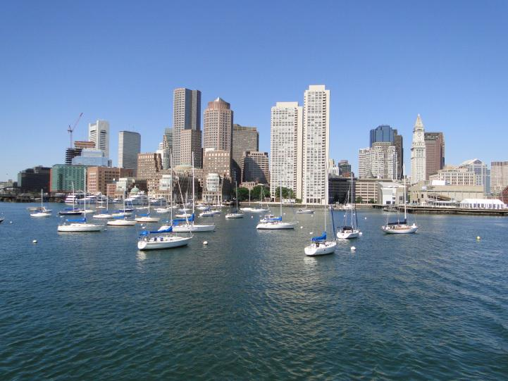 A city skyline with a large body of water in front of the buildings and boats at anchor.