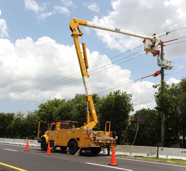 Photo of utility worker repairing raised electical lines