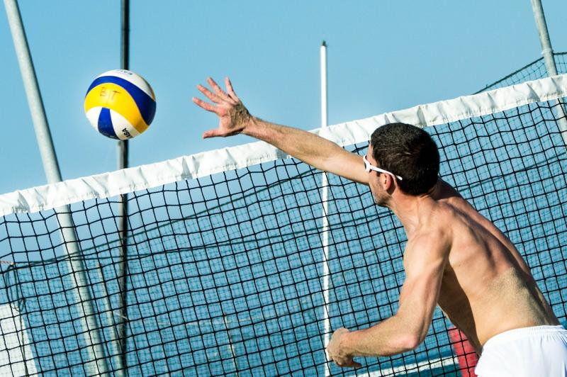 Photo of a man playing beach volleyball
