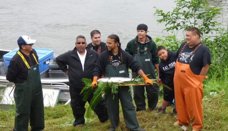 Group of people, with one carrying a whole salmon on a bed of cedar branches