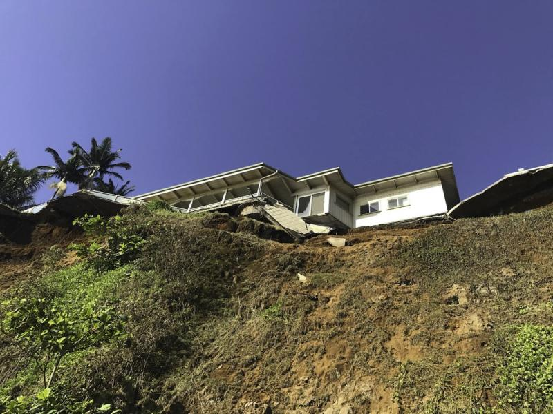 Beach-level view looking up at home with undercut cliff