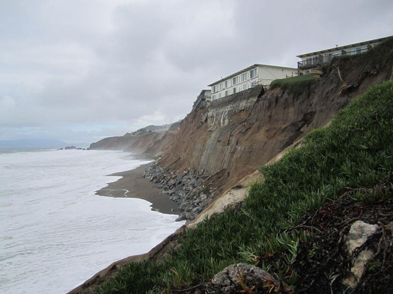House on top of a crumbling cliff above ocean waves