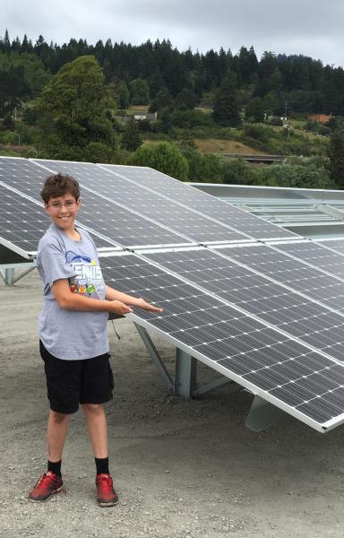 Boy next to solar panels