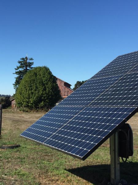 A solar panel near a barn