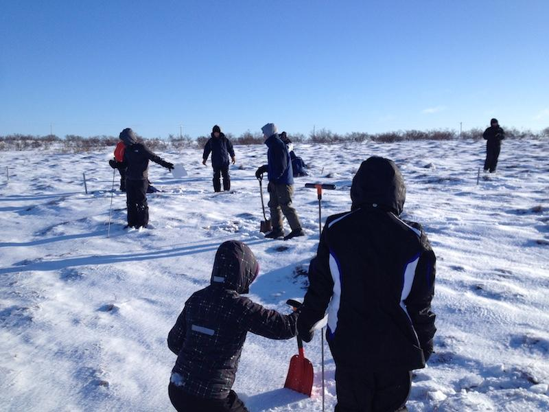 People on snowy surface with shovels and coring instruments