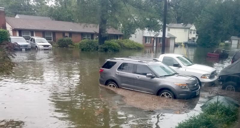 A flooded suburban street lined with homes and various automobiles submerged to their wheel wells in food waters.