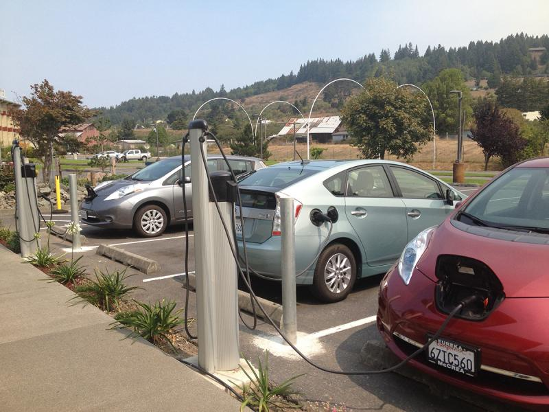 Two electric vehicles at charging stations
