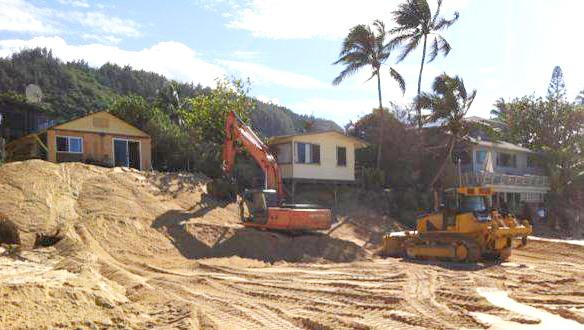 Bulldozers moving beach sand in front of houses
