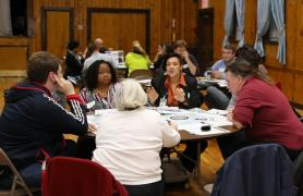 Adults holding discussions at three round tables
