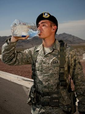 An airman drinks bottled water to stay hydrated