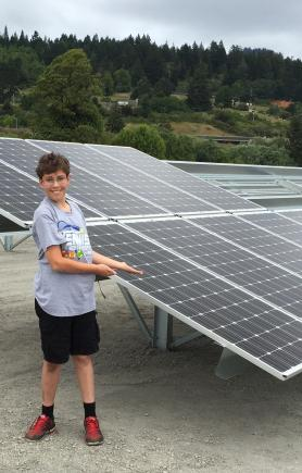 Boy next to solar panels