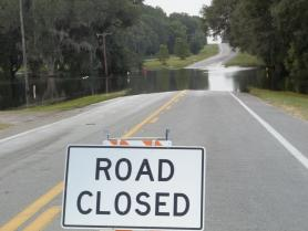 Road Closed sign in front of flooded roadway