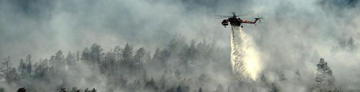 A helicopter drops water on the Waldo Canyon fire in June, 2012